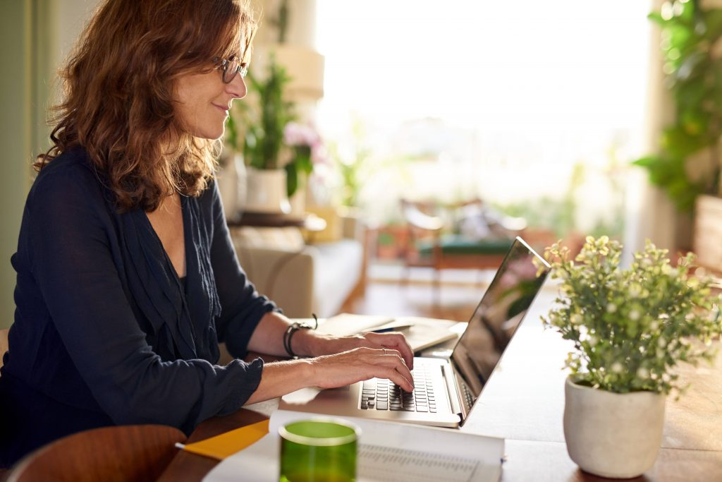 a young or middle-aged white women with red hair and glasses working on a laptop computer at home or an office, surrounded by green plants near a window