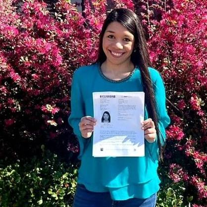 Destiny outside by a flowering bush and holding her drivers license document