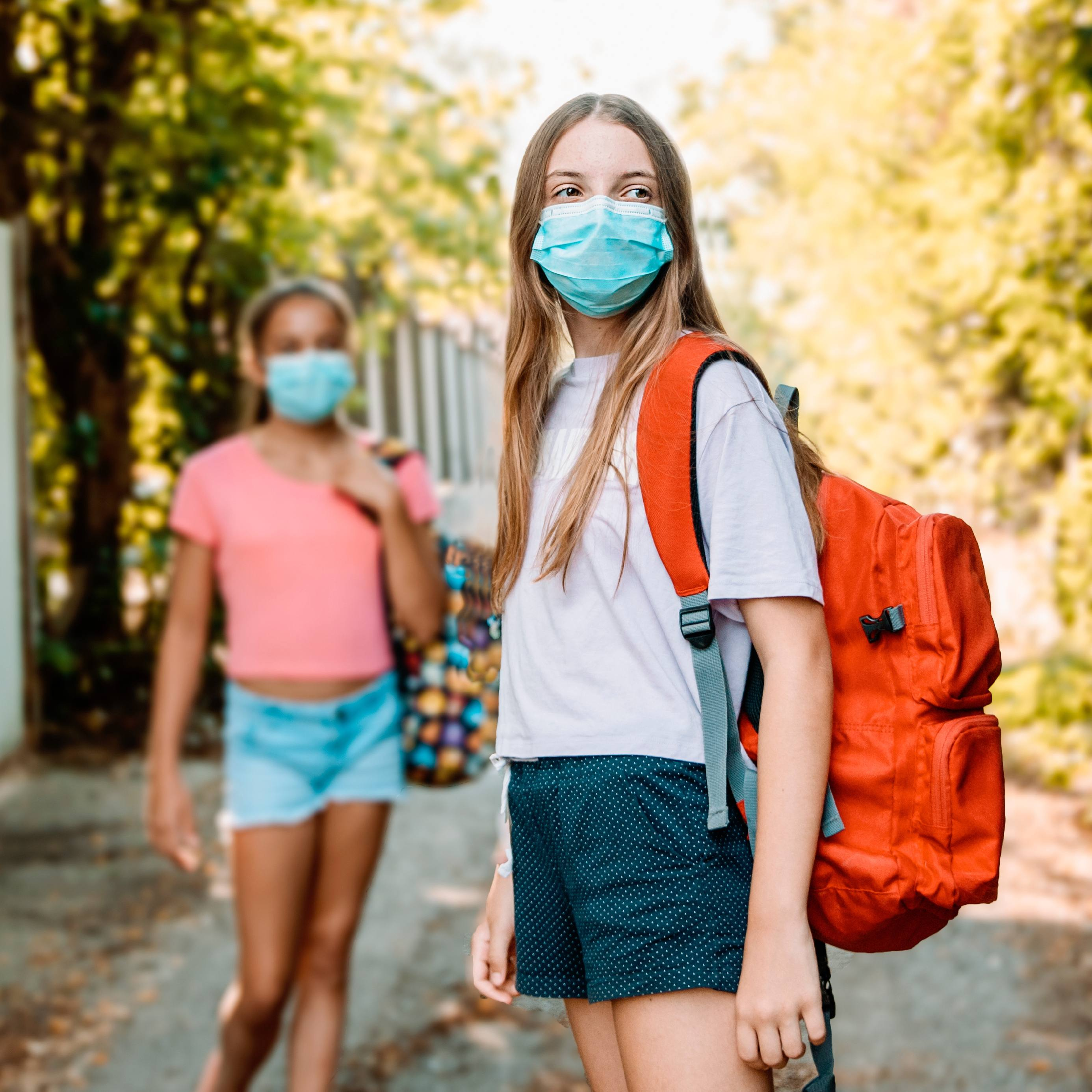 a young white teenage girl outside wearing a mask and a school backpack, walking with a friend