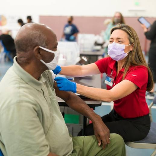 a Mayo medical staff person, white woman, administering a COVID-19 vaccine to an adult Black man, both wearing masks