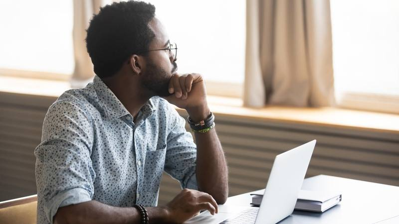 a middle aged Black man sitting at a computer looking thoughtfully out a window