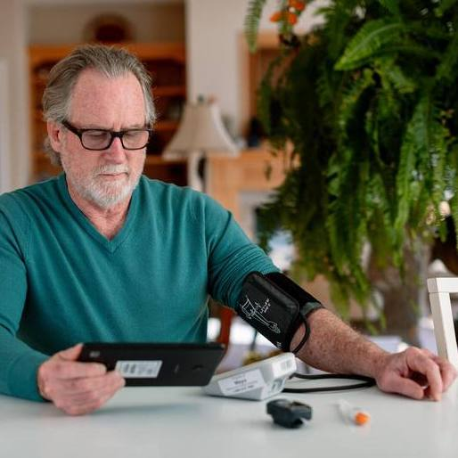 a white middle aged man wearing glasses and taking his blood pressure for home telehealth monitoring
