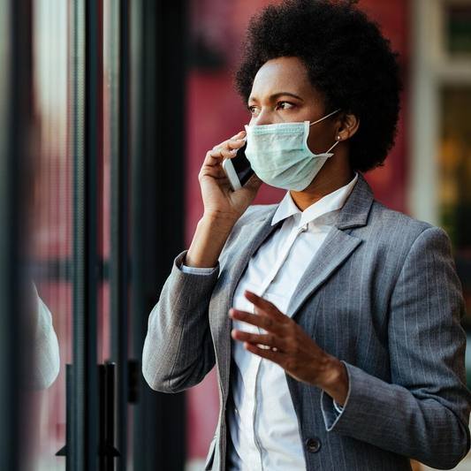 a young Black woman in a business suit standing by a window, wearing mask and talking on a phone