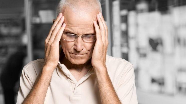 an elderly white man with grey hair looking sad, worried, forgetful holding his head with his hands