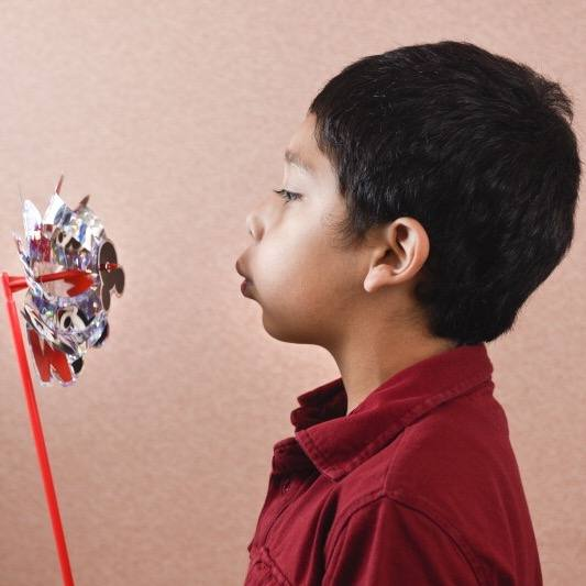 a young boy, perhaps Latino or Asian, blowing on a pinwheel to see it turn with the air