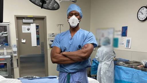 Dr. Okoroha in scrubs in operating room with mask