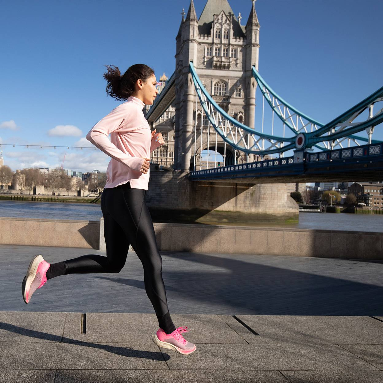 a young woman in exercise clothes running along the Thames River and bridge in London