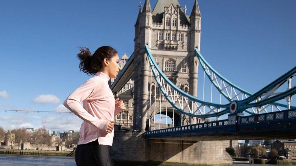 Una mujer joven en ropa deportiva corriendo a lo largo del río Támesis y el puente en Londres