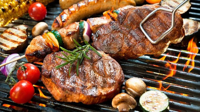 a grill filled with picnic foods like hamburgers, steaks, brats and vegetables
