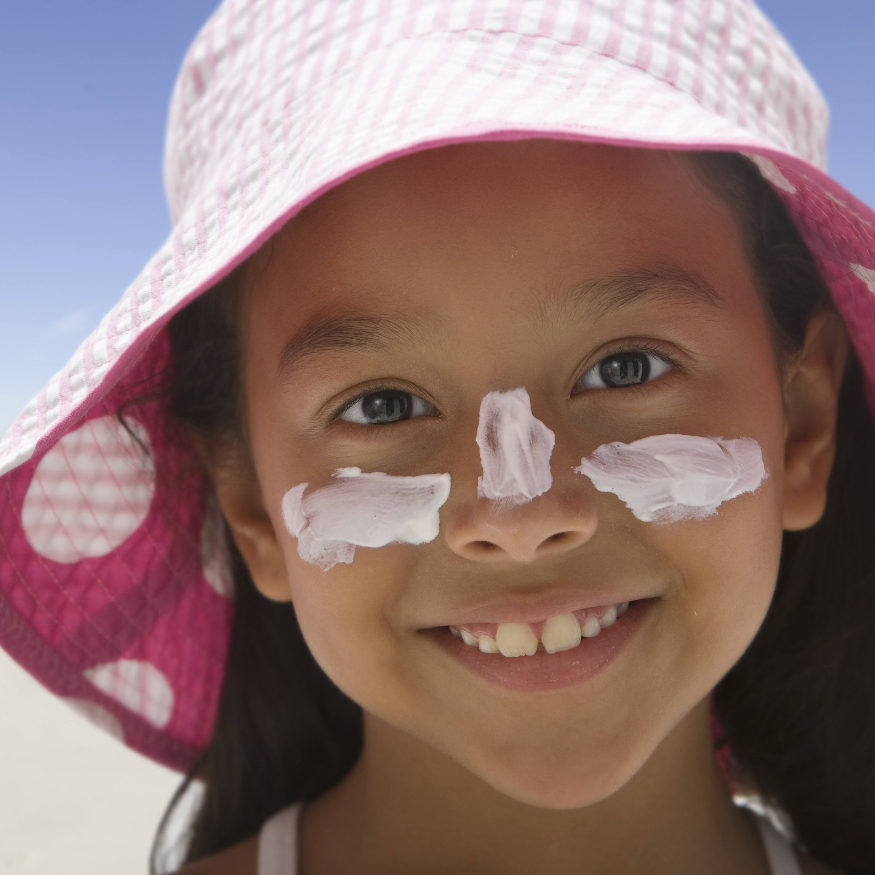 a little girl, perhaps Latina, at the beach smiling and wearing a sun hat, sunscreen