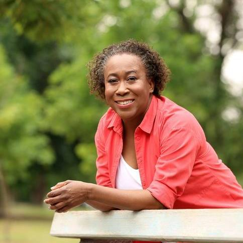 a middle aged Black woman outside, leaning on a fence, smiling and looking happy