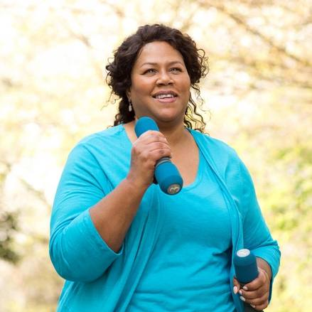 a middle aged Black woman outside, smiling while exercising, walking and carrying hand weights