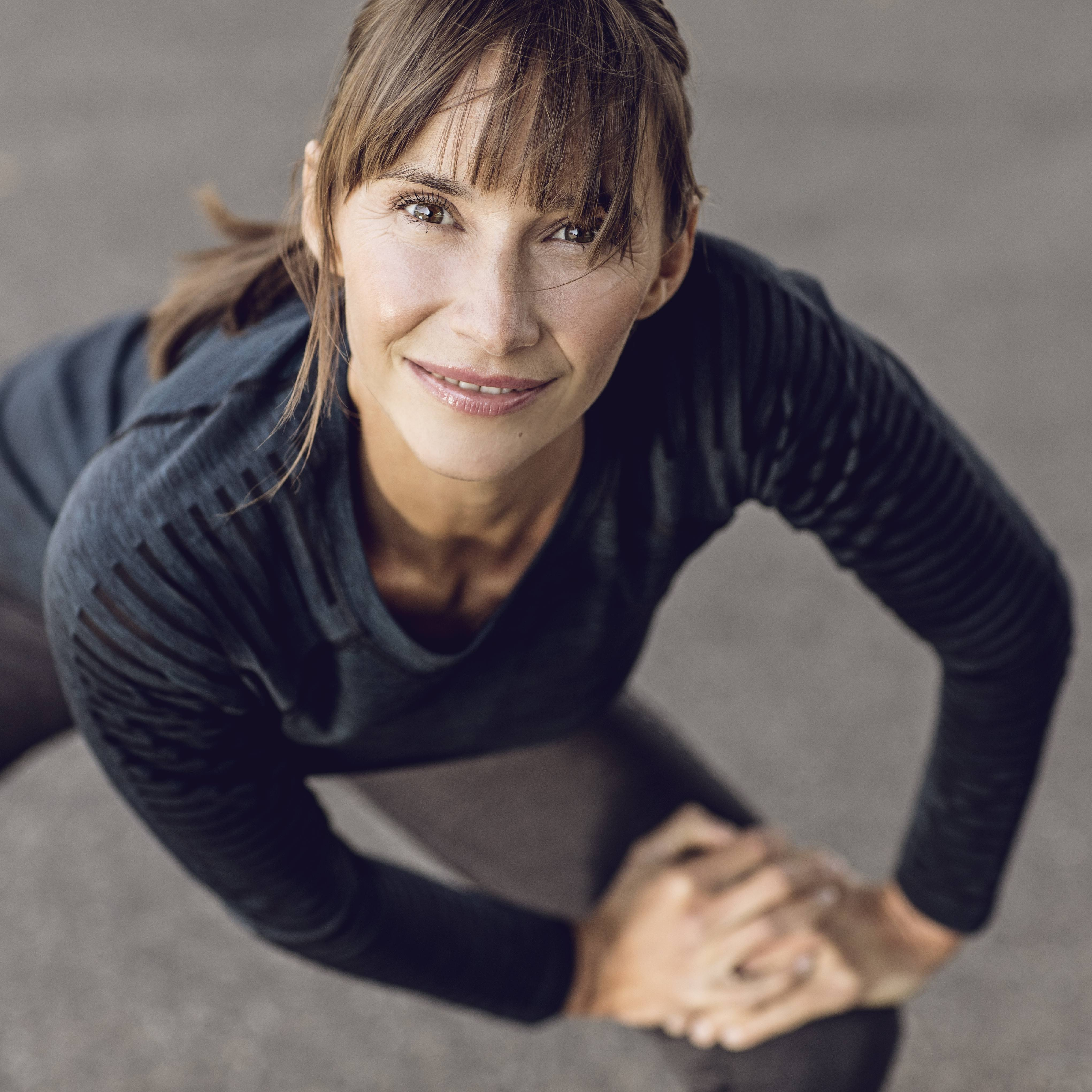 a middle aged white woman smiling and doing warmup exercise and stretching