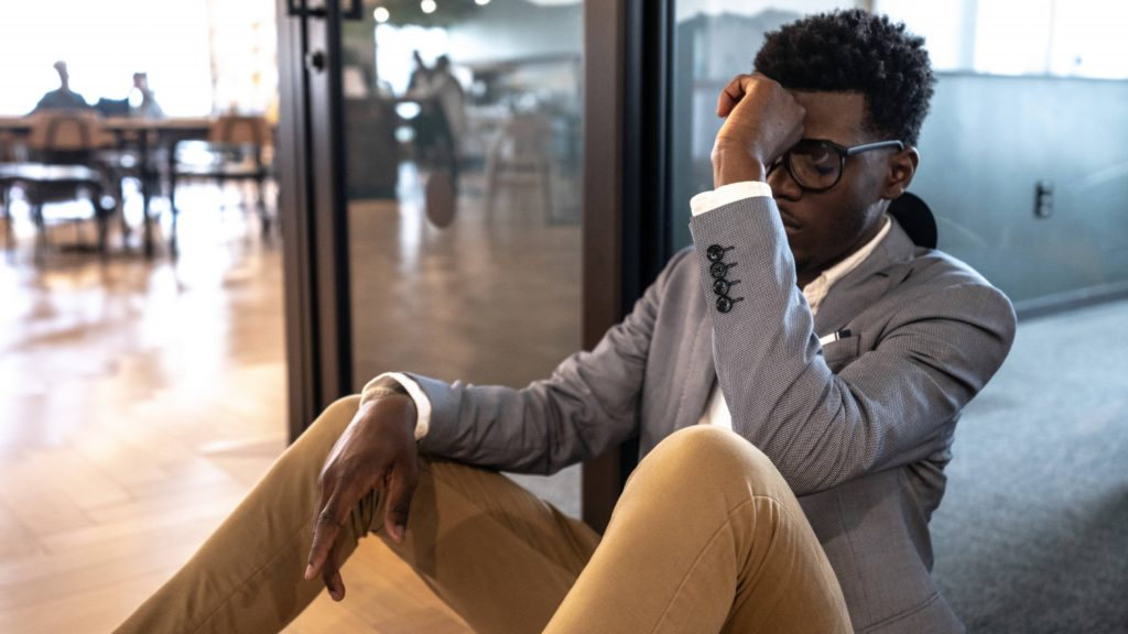 a young Black man in a business suit and sitting on the office floor alone looking sad, worried, anxious