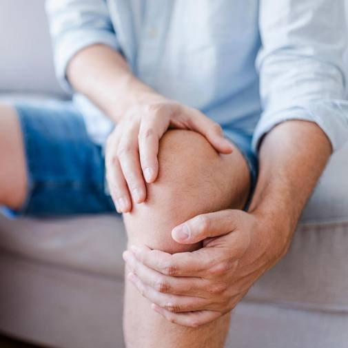 a young white adult sitting on a couch in shorts and holding a knee as in pain or injury