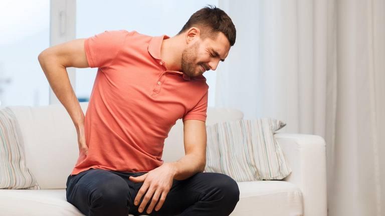 un joven sentado en un sillón se frota la zona lumbar de la espalda porque siente dolor, tal vez procedente del riñón