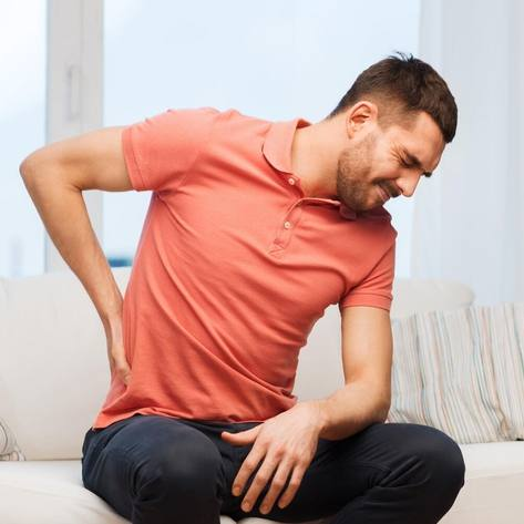 a young white man sitting on a couch rubbing his lower back because it hurts, perhaps in kidney pain