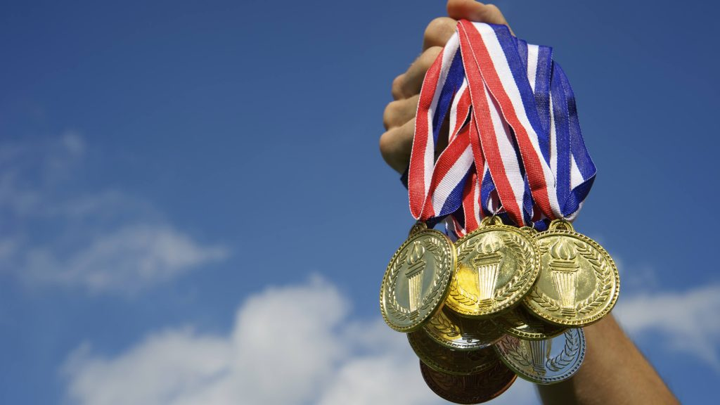 closeup of a person's arm holding up a handful of Olympic gold medals with ribbons against a blue sky