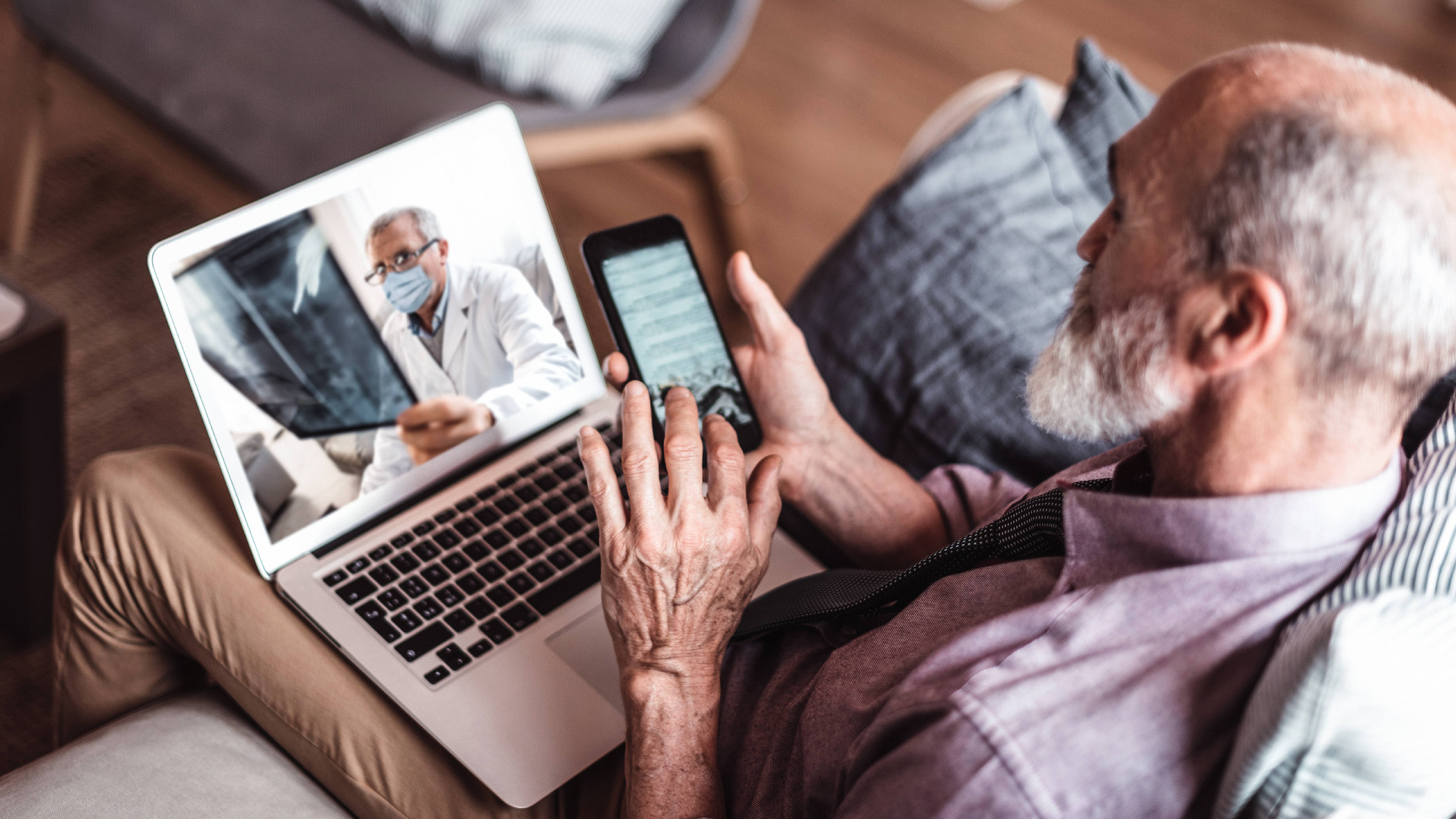 older white man sitting on a couch with his iPad during a telemedicine conference with a doctor