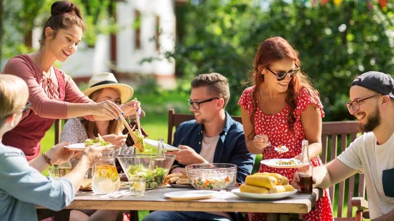 jóvenes amigos y familiares sentados afuera bajo el sol en una mesa de picnic