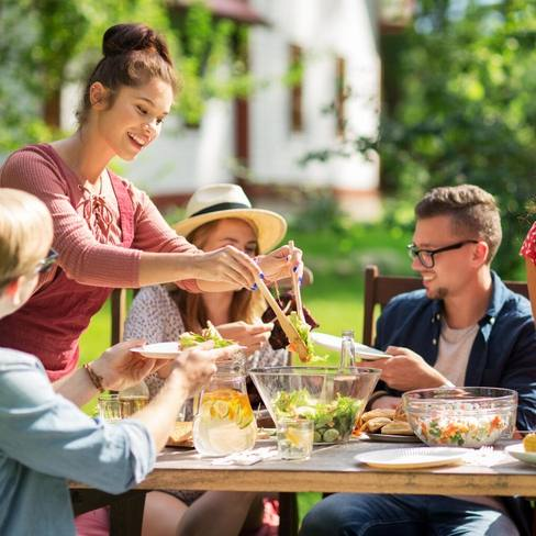 young friends and family sitting outside in the sunshine at a picnic table