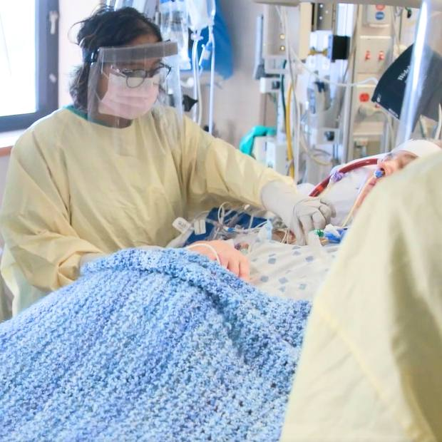 Mayo Clinic medical personnel in full PPE tending to a patient with COVID-19 in a hospital bed