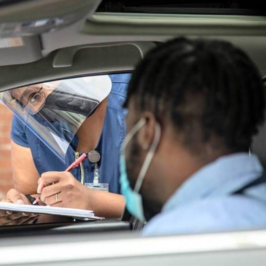 a Black man in a car at a COVID-19 testing center