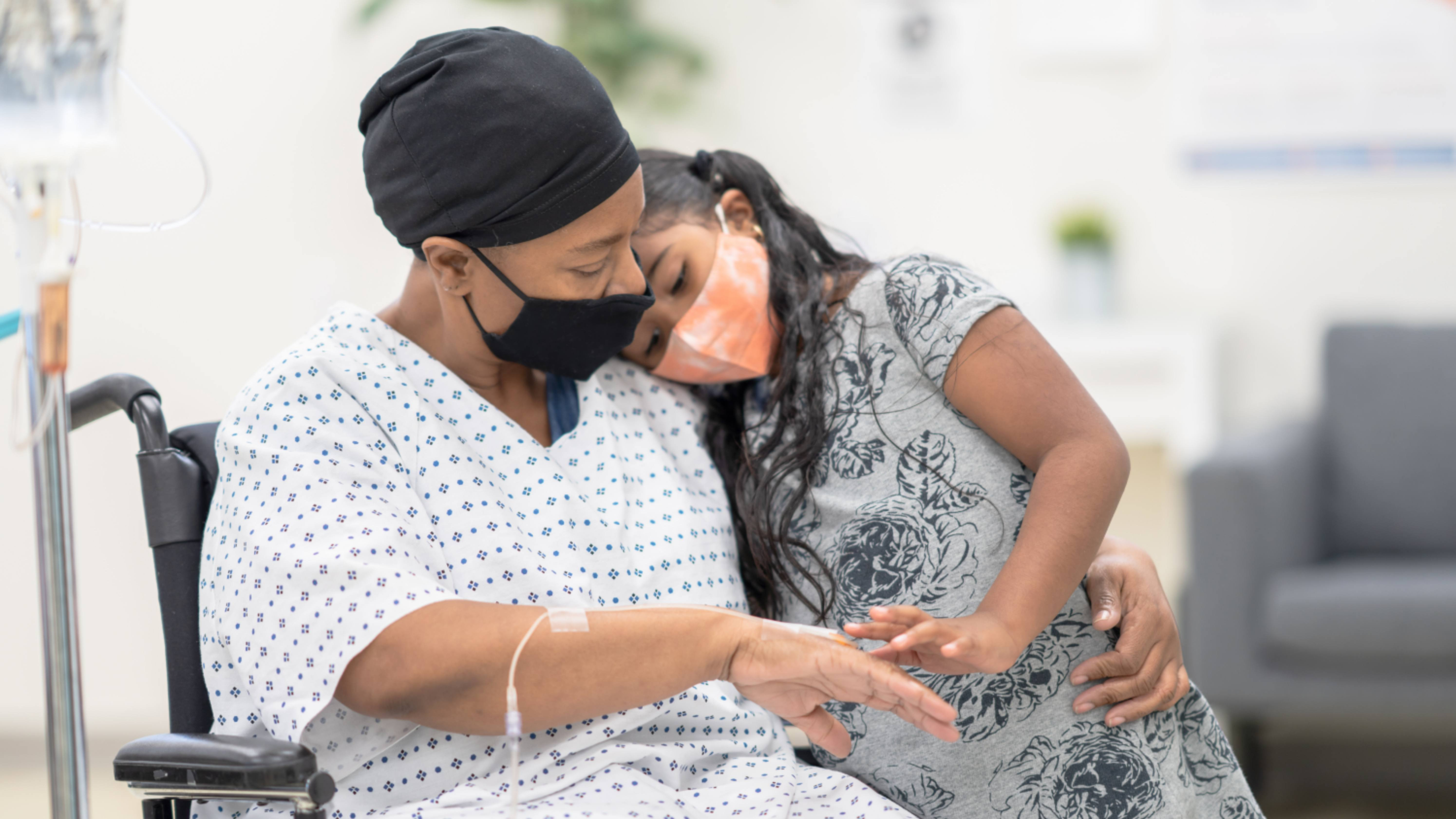 a Black woman with cancer in a wheelchair, with a chemotherapy IV, and little girl hugging her, both wearing masks