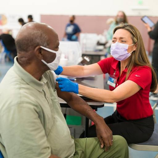 a Mayo Clinic medical staff person, a white woman, administering a COVID-19 vaccine to a Black man, both wearing masks in a vaccine clinic