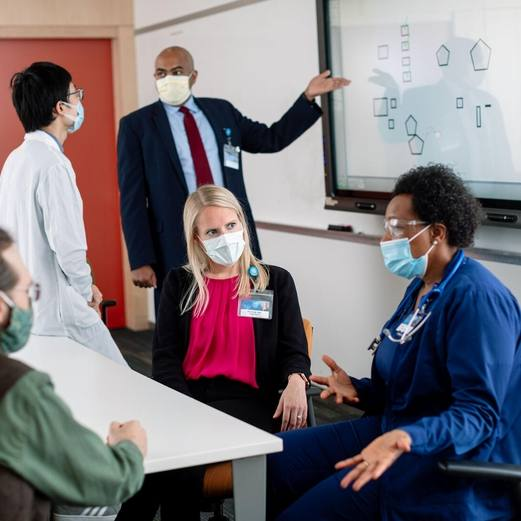 a diverse group of Mayo Clinic employees wearing masks in a conference room discussing medical topics