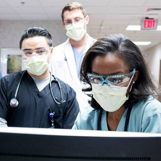 a diverse group of Mayo Clinic medical care givers all wearing masks and looking over patient information on a computer