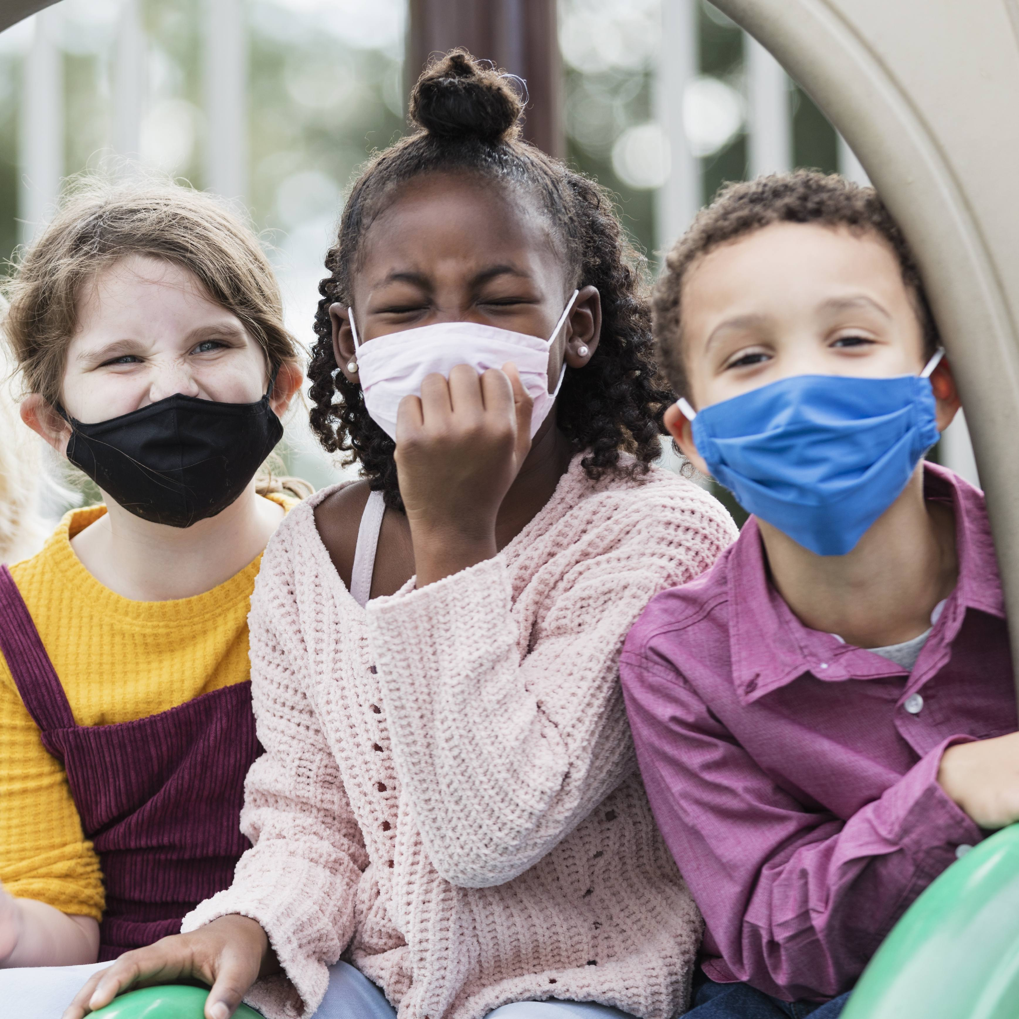 a diverse group of elementary school aged children, wearing masks and outside on a playground