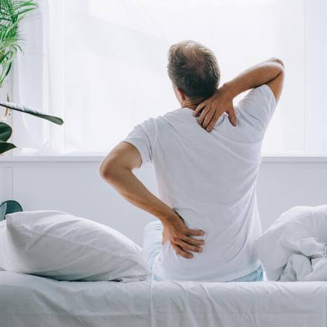 white man in a t-shirt facing a window sitting on a bed holding his neck and back in pain