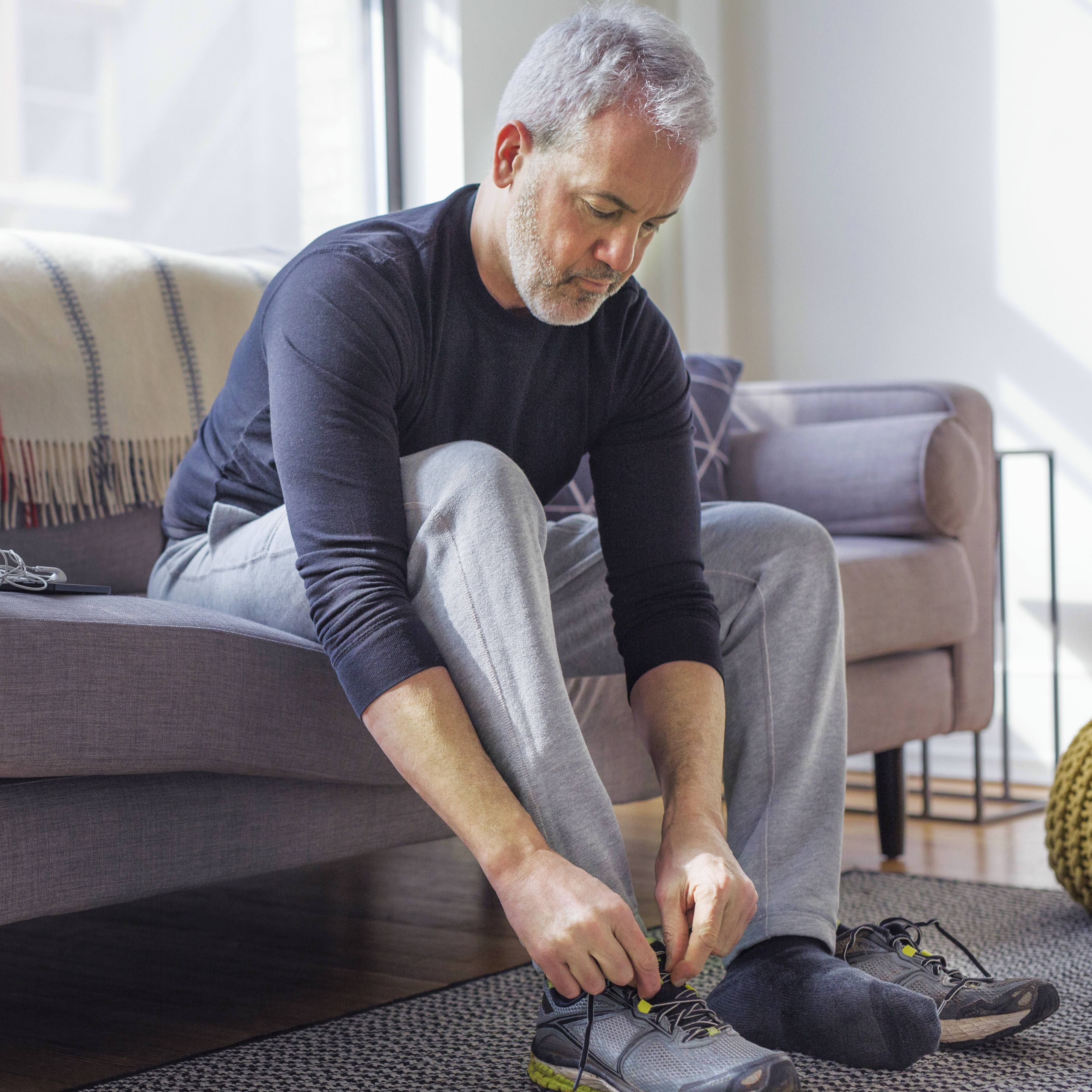 a middle aged white man in sweatpants sitting on a couch and tying exercise shoes