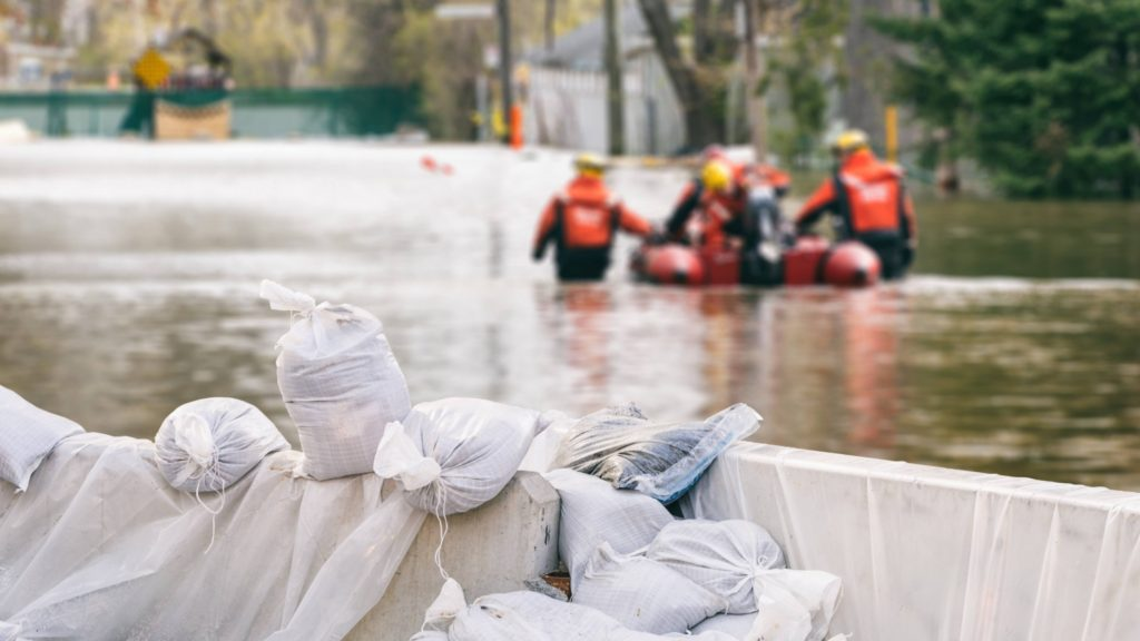 a storm flooded stream or street with sandbags and emergency teams with a rescue raft