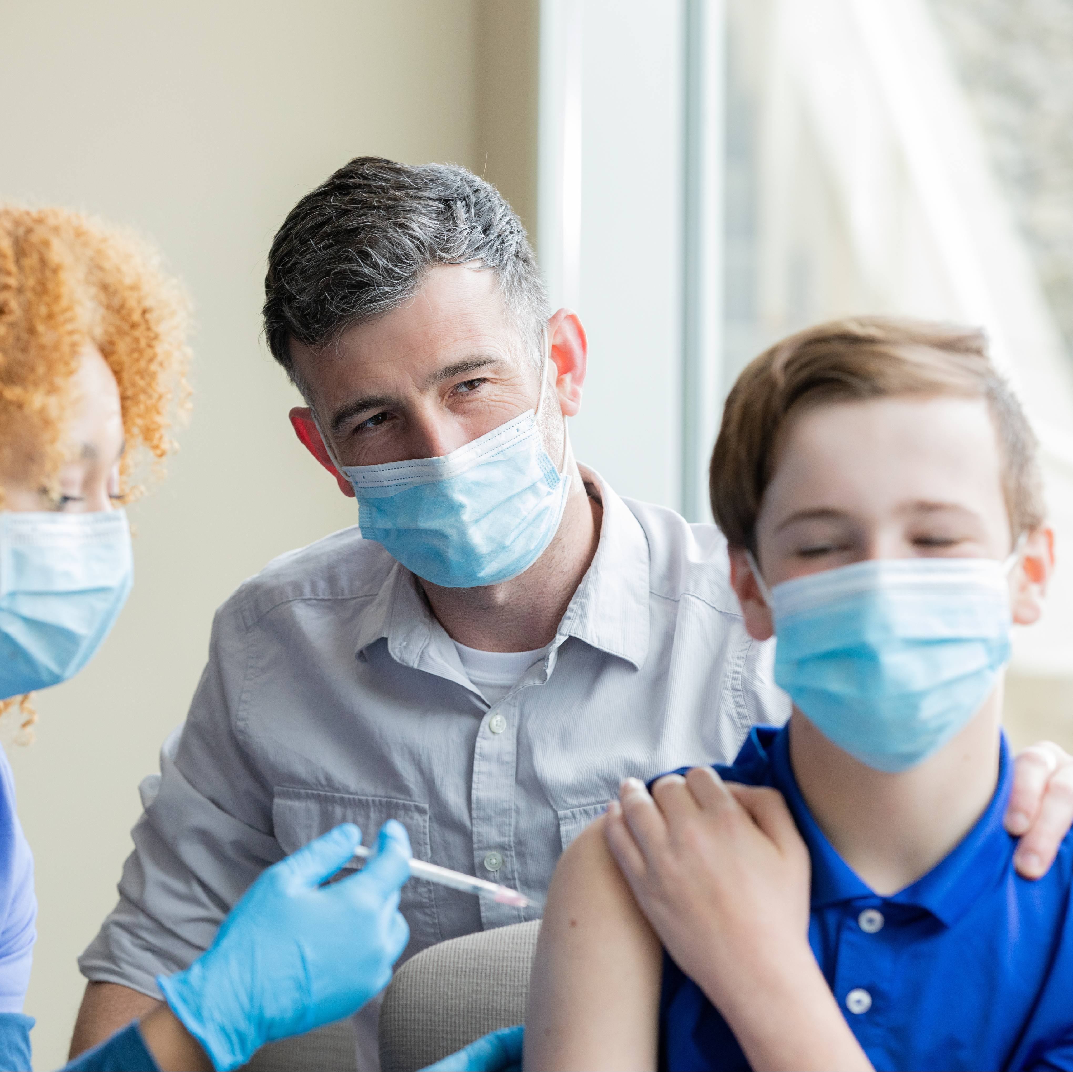 a white teenage boy, with an adult and a Black health care provider administering a vaccine, all wearing masks