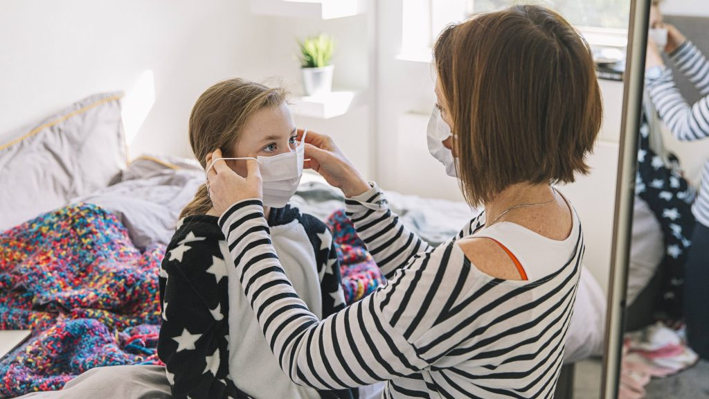a white woman, a mother, wearing a mask and helping a young girl, perhaps her daughter, put on a mask during COVID-19 pandemic