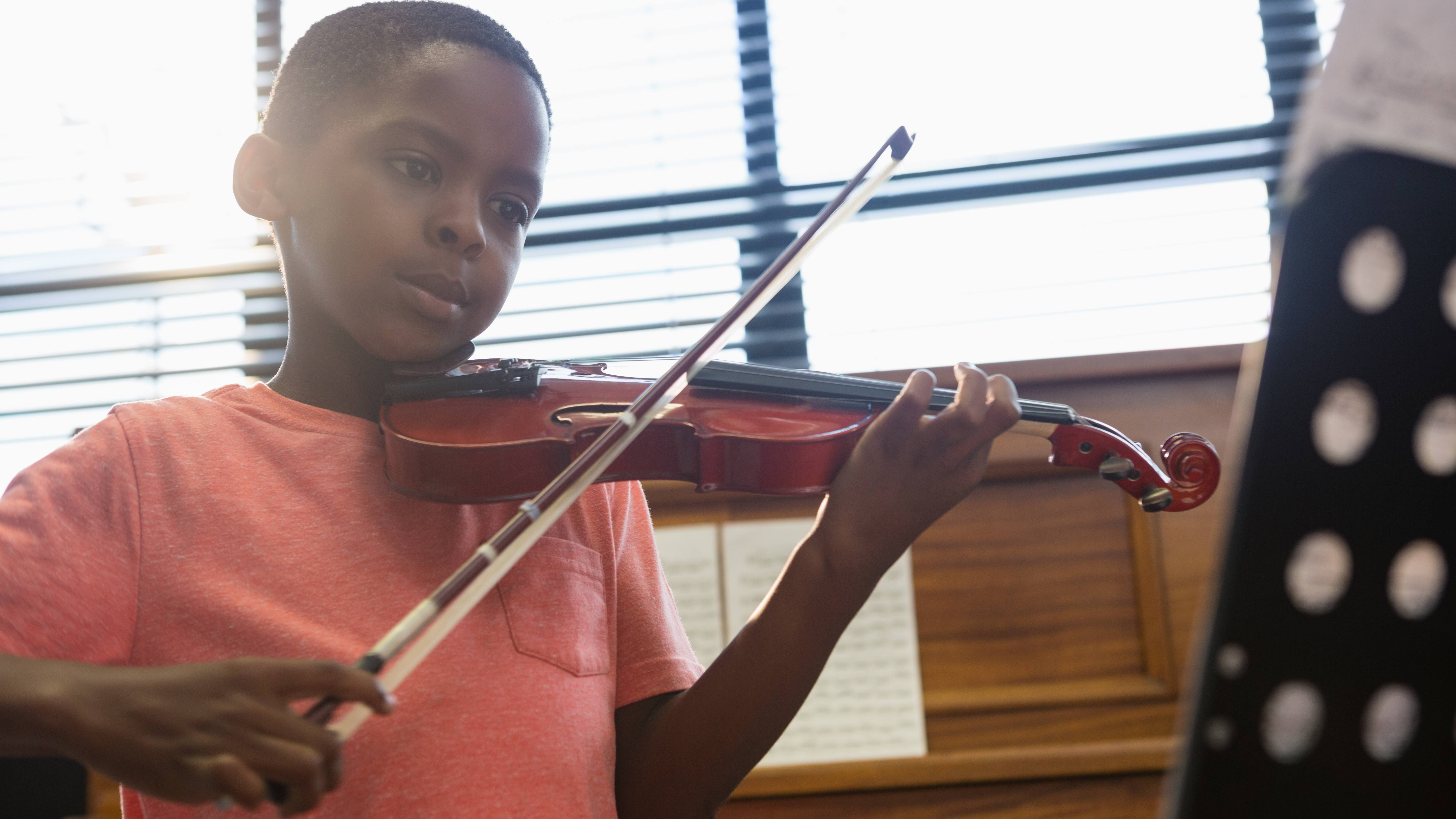 a young Black boy in an orange shirt playing a violin, with sheets of music on an instrument stand