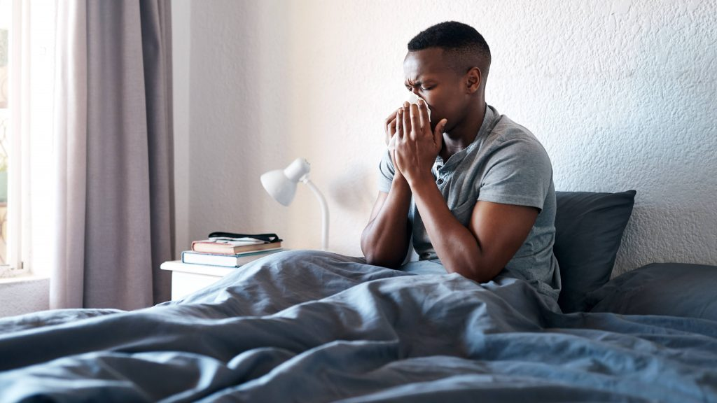 a young Black man sick in bed, coughing and blowing his nose