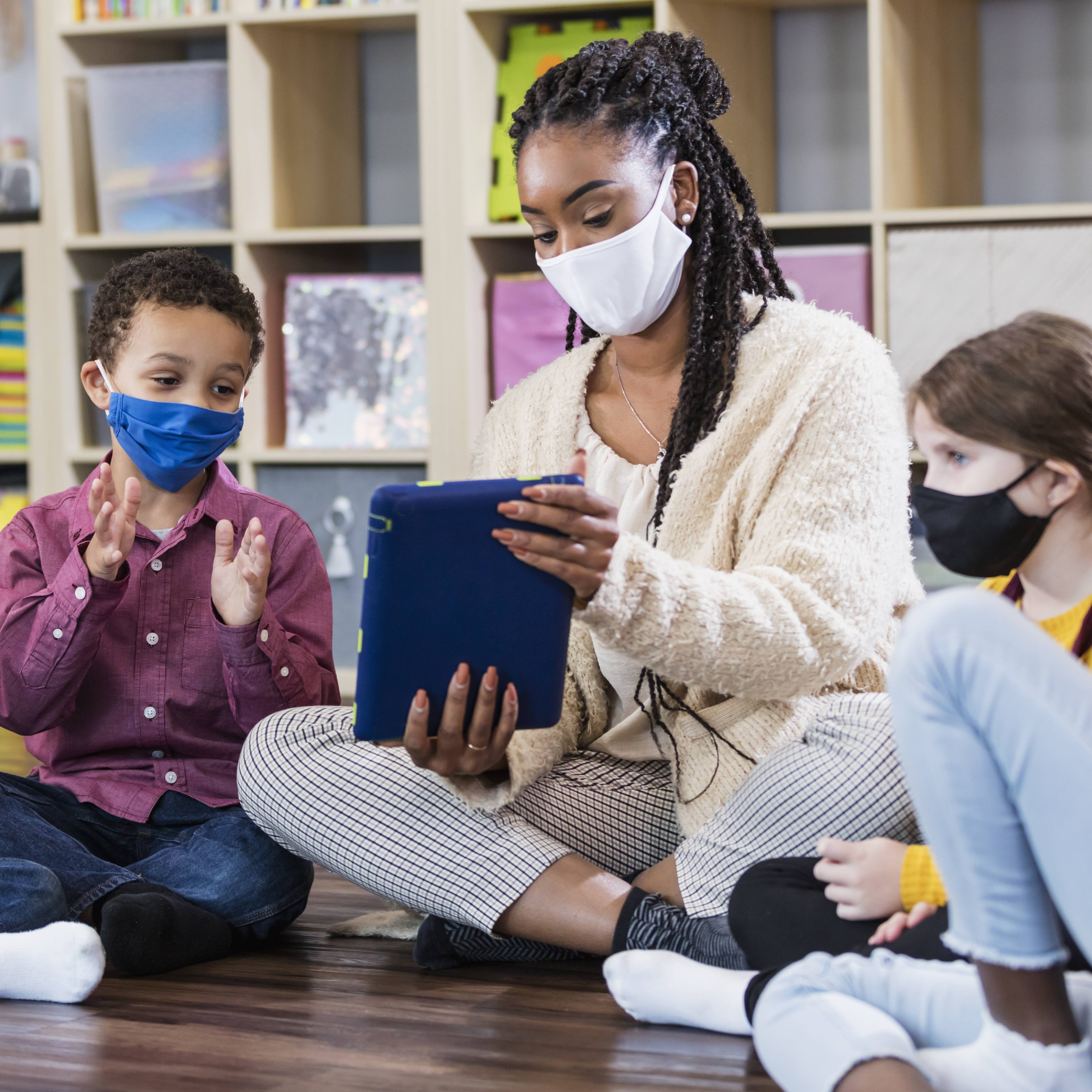 a young Black woman, teacher sitting on classroom floor reading to school children, all wearing masks