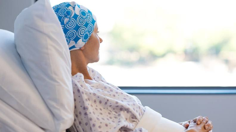 a young white woman in a hospital bed, looking out a window, wearing a headscarf because of chemo treatment for cancer