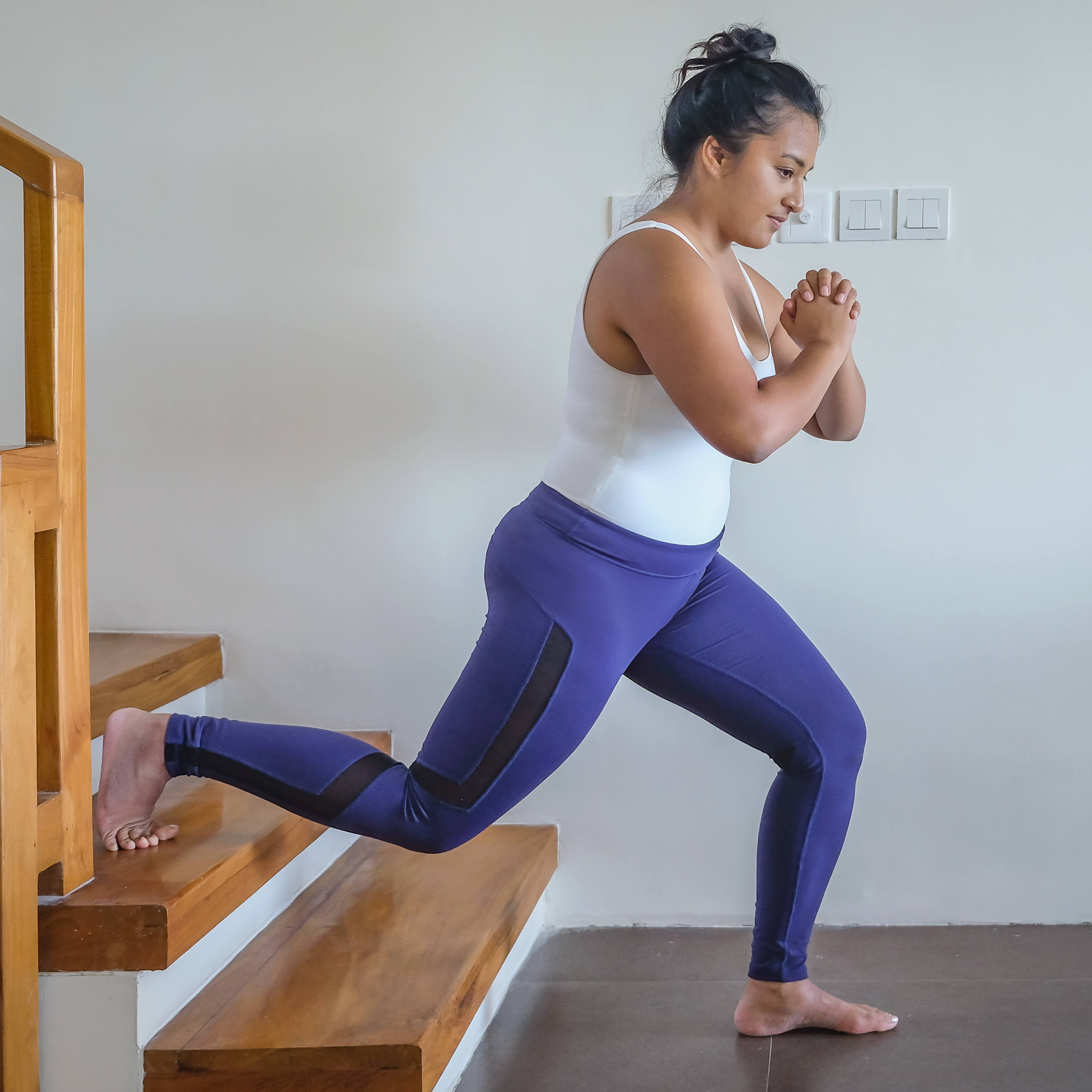 a young woman, perhaps Latina or Asian, in workout clothes exercising on her stairs at home
