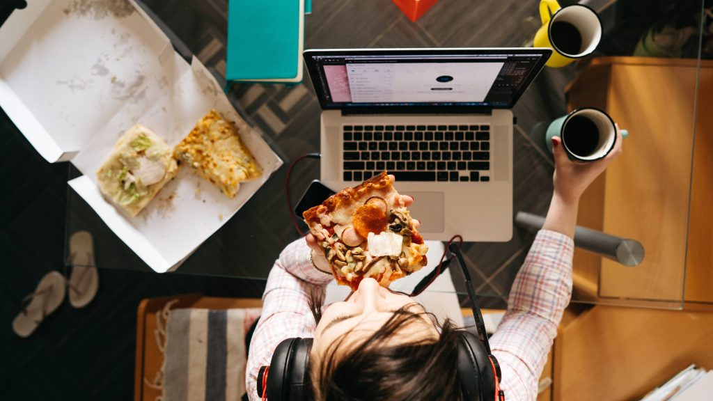 a young woman sitting at a home computer eating pizza with two cups of coffee nearby, maybe stressed with work