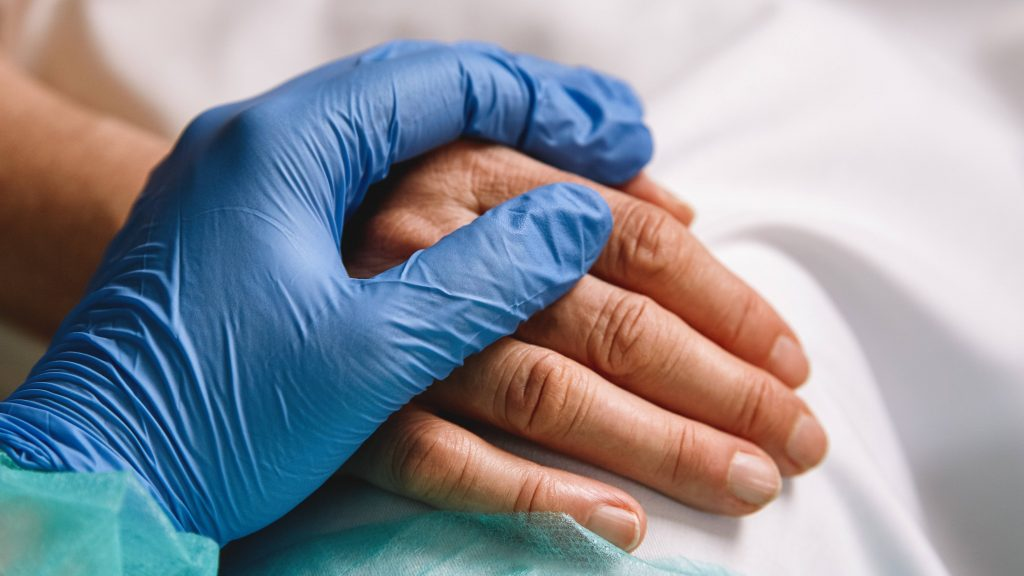 closeup of a health care provider's hand with a medical glove holding a patient's hand in a hospital bed