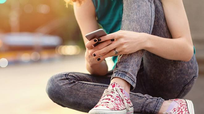 a young white person, a teenager, wearing jeans and tennis shoes sitting with legs crossed using a mobile cell phone