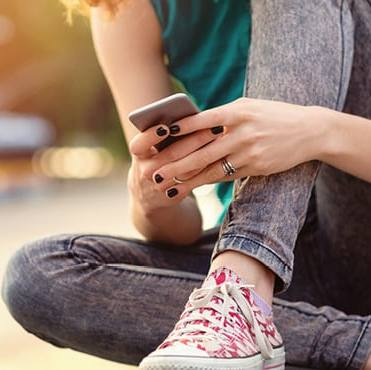 a young white person, a teenager, wearing jeans and tennis shoes, sitting with legs crossed using a mobile cell phone