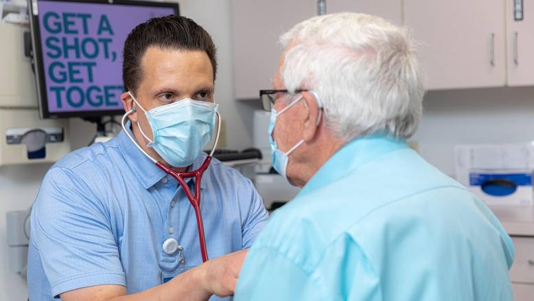 Mayo Clinic Health System physician wearing a mask and examining a patient, both are white males