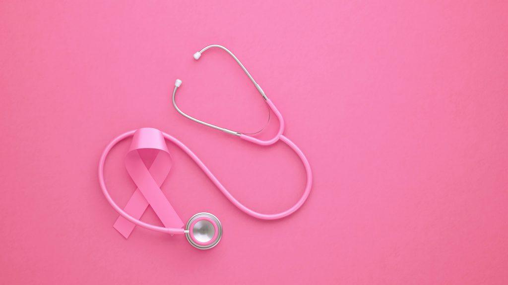 Sobre un fondo de color rosa aparecen un estetoscopio rosa y una cinta rosa para concienciación sobre el cáncer de mama