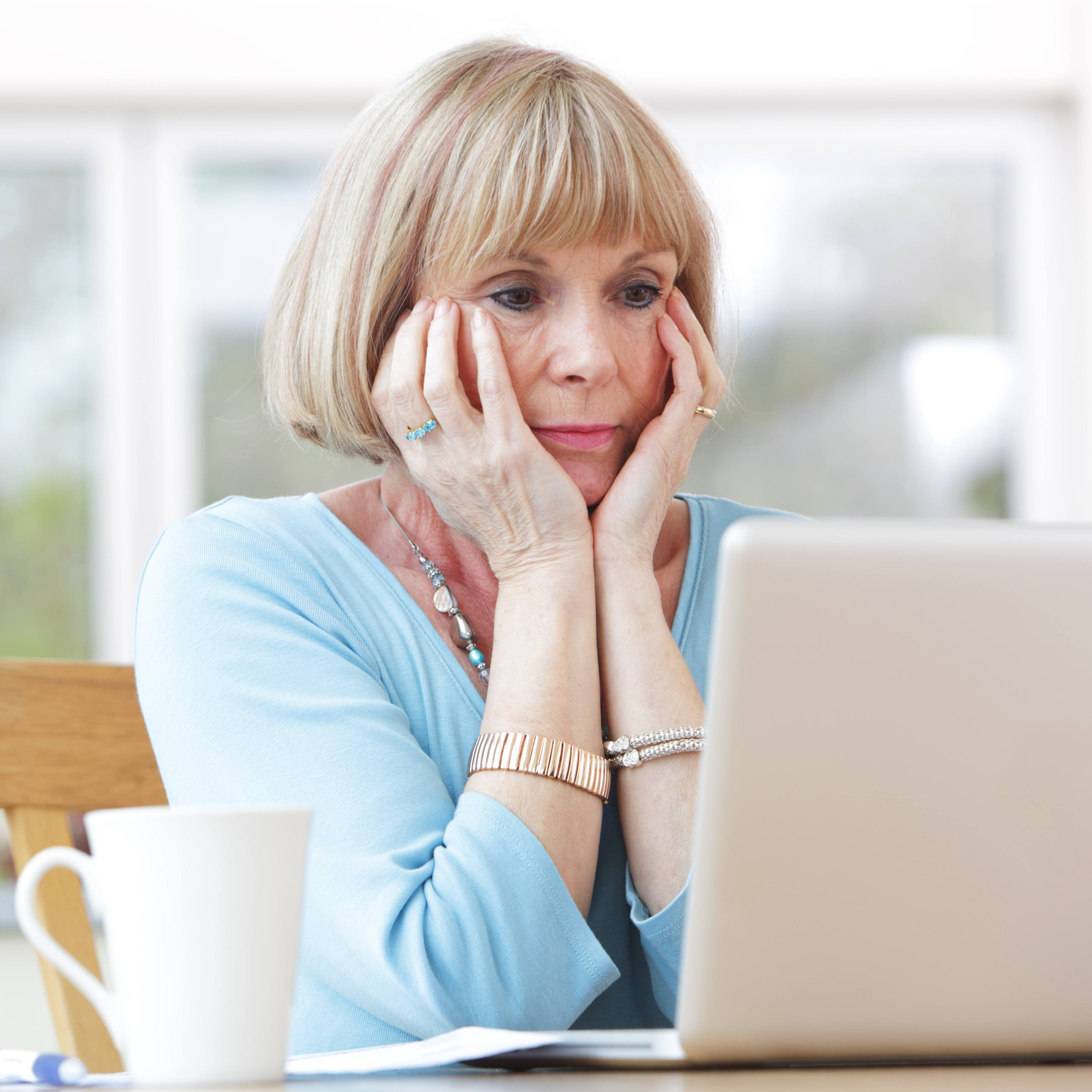 a middle-aged white woman worried, concerned with her head in her hands looking at a computer laptop