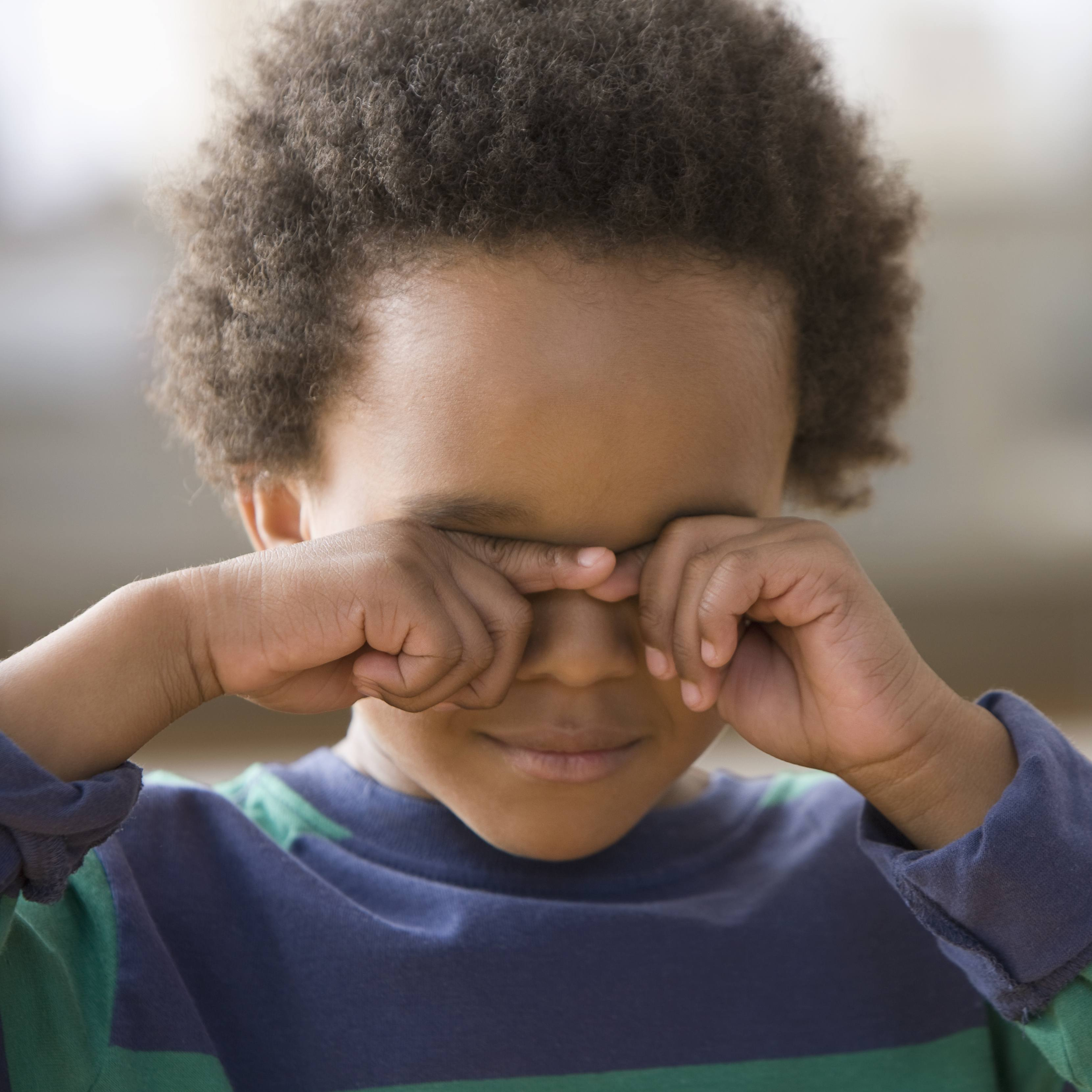 a young Black boy looking sad, scared and wiping his eyes